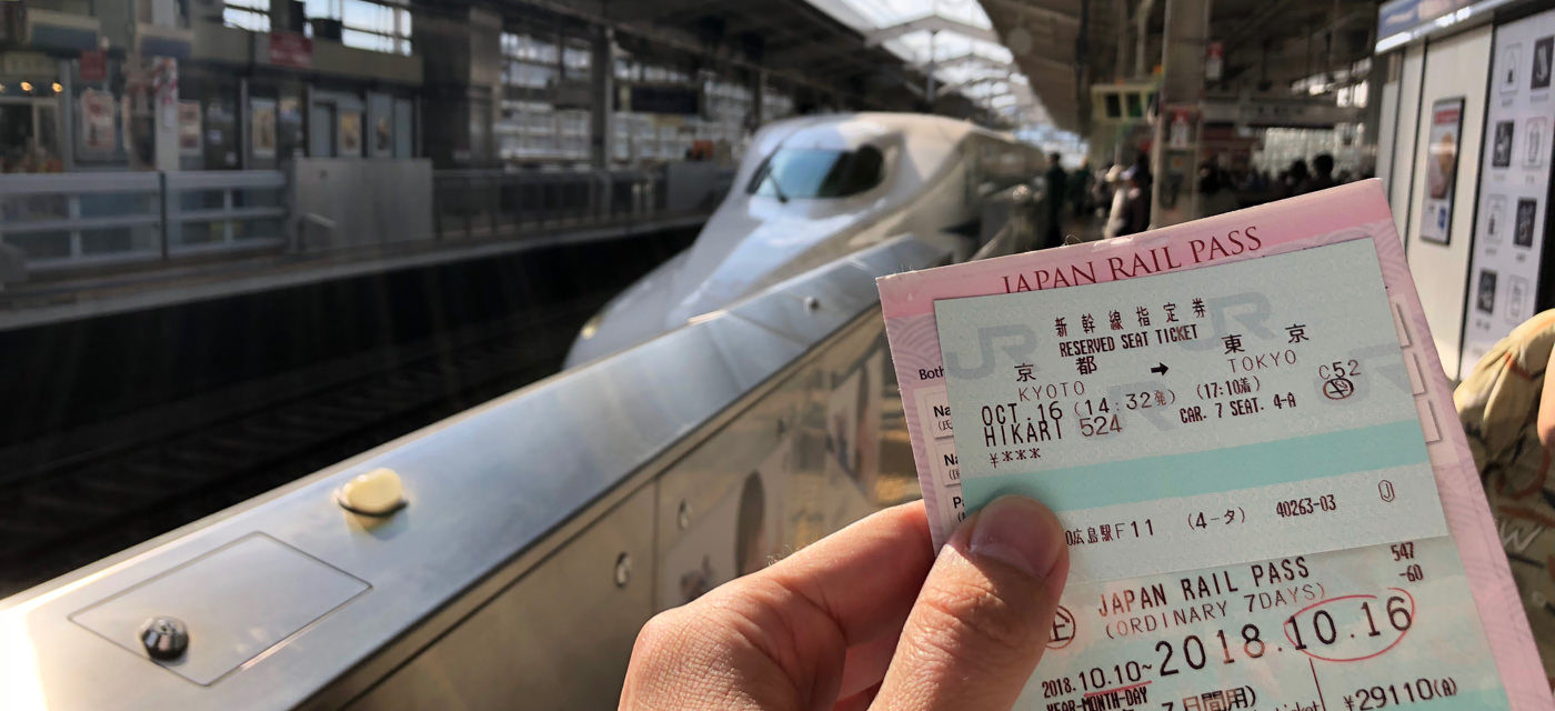 Holding a Japan Rail Pass on a Shinkansen platform