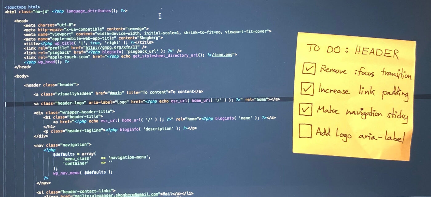 Code shown on a monitor with a post-it note with a to do list stuck to it