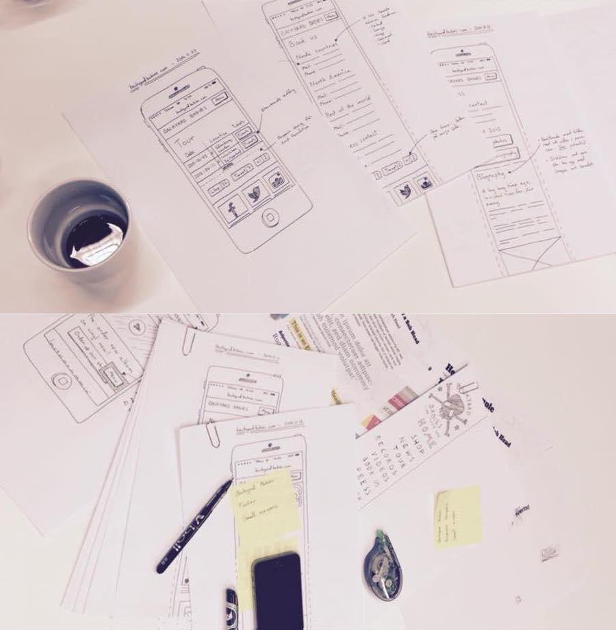 Lots of paper wireframes and some notes on a table