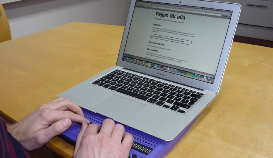 A user browsing Fejjan För Alla on a laptop using a Braille keyboard.