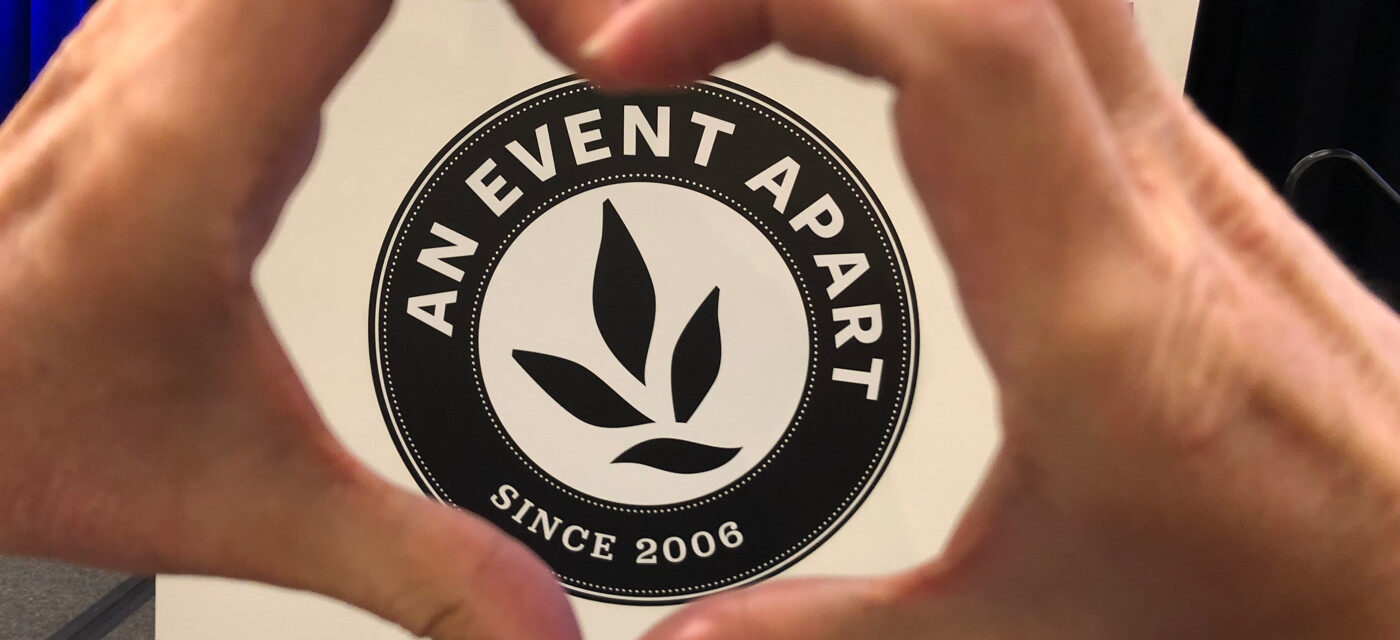 Two hands forming the shape of a heart around the An Event Apart logo