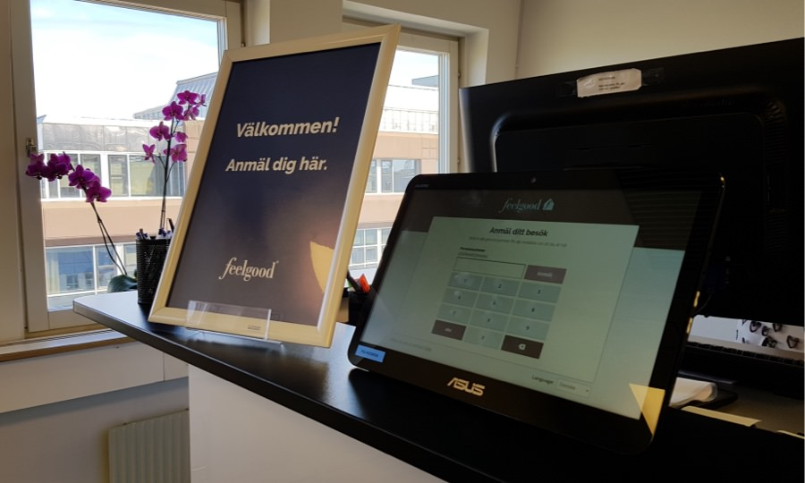 The tablet running Feelgood Visitor Registration standing on a reception desk next to a poster telling visitors to register here.